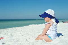 Baby girl sitting on the beach looking at the ocean Stock Image