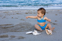 Baby girl sitting on the beach pointing Stock Photos