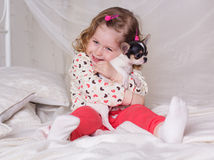 Baby girl is sitting on bed and hugging dog Royalty Free Stock Photo