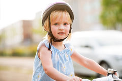 Baby girl sitting on bicycle Royalty Free Stock Photos