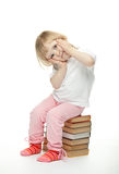 The baby girl is sitting on the books Royalty Free Stock Photo