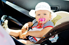 Baby girl sitting in car Stock Images