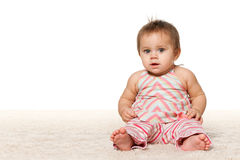 Baby girl is sitting on the carpet Royalty Free Stock Image