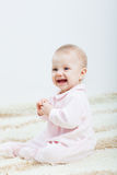Baby girl sitting on the carpet Royalty Free Stock Images