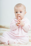 Baby girl sitting on the carpet Royalty Free Stock Photography