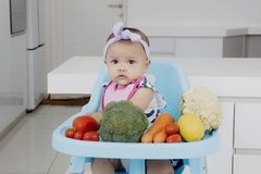 Baby girl sitting on chair with vegetables Royalty Free Stock Image