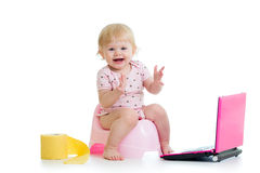 Baby girl sitting on chamberpot with notebook Royalty Free Stock Photos