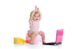 Baby girl sitting on chamberpot with notebook stock photos