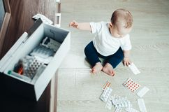 Baby, girl sitting on the floor in the hands of pills. Pulled out of the box or out of the closet stock photo
