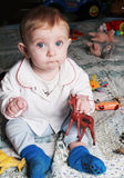 Baby girl sitting on the floor in her room stock photos