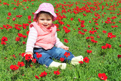 Baby Girl Sitting in Flowery Field Stock Image