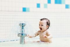 Baby girl sitting in front of little fountain, laughing. royalty free stock image