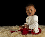 Baby girl sitting on a fur rug Stock Photos