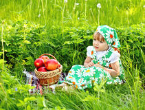 Baby girl is sitting on a glade and eating apples Royalty Free Stock Images