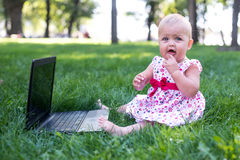 Baby girl sitting on the green grass Stock Images
