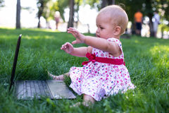 Baby girl sitting on the green grass Stock Photography