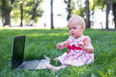 Baby girl sitting on the green grass Stock Image