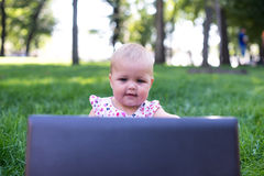 Baby girl sitting on the green grass Royalty Free Stock Photography