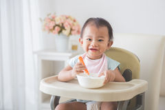 Baby girl sitting on high chair and feed her self Royalty Free Stock Photos