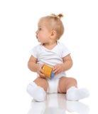 Baby girl sitting and holding jar of child mash puree food Stock Photo