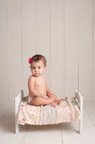 Baby Girl Sitting on a Little Bed Royalty Free Stock Images