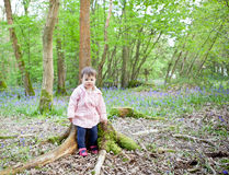 A baby girl sitting on the log in the forest Royalty Free Stock Images
