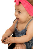 Baby girl sitting looking sideways with her mouth open Royalty Free Stock Photo