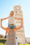 Baby girl sitting on mothers shoulders in pisa Stock Image