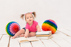 Baby girl sitting near multicolored balls Stock Photos
