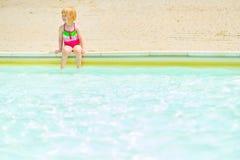 Baby girl sitting near pool Royalty Free Stock Image