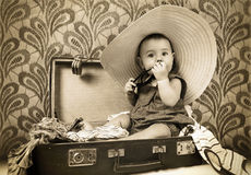 Baby girl sitting into the old suitcase Royalty Free Stock Images
