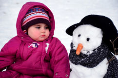 Baby girl sitting outdoor next to snowman Stock Images