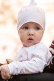 Baby girl sitting in a perambulator Stock Image