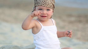 Baby girl sitting and playing on the beach stock footage