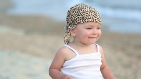 Baby girl sitting and playing on the beach stock video