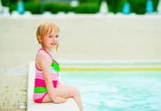 Baby girl sitting at poolside Stock Photography
