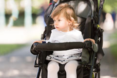 Baby girl sitting in the pram Royalty Free Stock Image