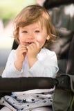 Baby girl sitting in the pram Royalty Free Stock Photos