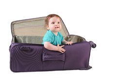 Baby girl sitting in a purple suitcase Royalty Free Stock Photography