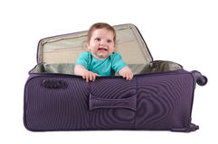 Baby girl sitting in a purple suitcase Stock Images