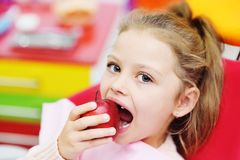 Baby girl sitting in a red dental chair smiling with a red Apple in her hands. stock photos