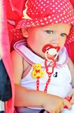Baby girl sitting in red stroller Stock Photography