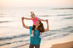 Baby girl sitting on shoulders of mother on beach. Happy baby girl sitting on shoulders of mother on beach in the evening Stock Images