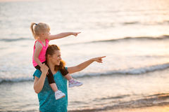 Baby girl sitting on shoulders of mother on beach Royalty Free Stock Photography
