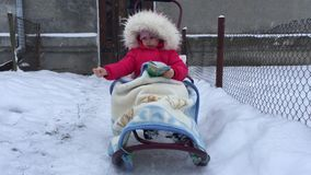 Baby girl is sitting on a sleigh hiding in a blanket, catching the flying snowflakes and reading a book. Baby girl is sitting on a sleigh hiding in a blanket stock video footage