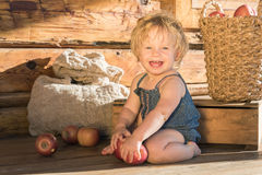 Baby Girl sitting and Smiling near Wooden Barn Stock Images