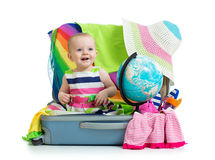Baby girl sitting in suitcase with globe Royalty Free Stock Photos