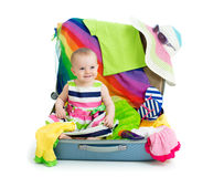 Baby girl sitting in suitcase with things Stock Photography