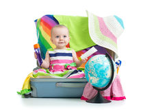Baby girl sitting in suitcase with things for Royalty Free Stock Images