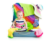 Baby girl sitting in suitcase with things for Stock Images